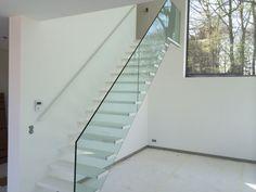 Zwevende trap in witte kunststof (corian) met glasbalustrade