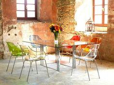chaises transparentes multicolores, table à manger en métal et verre, ambiance rustique et sol en béton