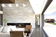 bates masi architects stone fireplace wall glass wall sliding doors cement floor architecture modern