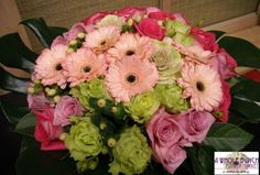 Roses, gerbera, hypericum berries, and other seasonal flowers make up this arrangement.