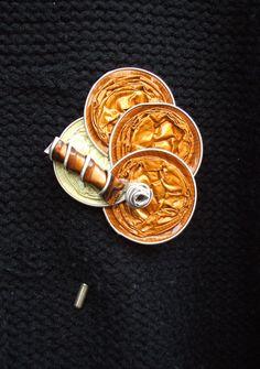 Diseño de Broches de alfiler. Colección Pirulillo.  Realizado con cápsulas nespresso color dorado oscuro y blanco rayados sobre base de broche de alfiler.  Bisutería, Accesorios y Complementos de Diseño. Fabricado de manera totalmente artesanal y 100% hecho a mano, lo que le confiere a cada complemento un carácter único y personal.  http://lacrisalidadelamariposa.wordpress.com/2014/03/23/broche-alfiler-02/