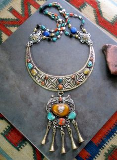*Antique Tibetan Jewelry Necklace comes via Tibetan traders bringing old pieces like to Kathmandu Nepal. Made of orately handcrafted Brass and Silver; the elaborate central piece in the shape of a crescent moon was handcrafted in brass, and studded with Turquoise, Red Coral, and Real Tibetan Amber.