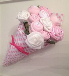A beautiful small bouquet for a new baby girl! A perfect item for a baby shower/maternity leave/new mum gift. It contains: 1 hat, 1 bib, 1 pair