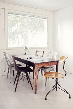 combinación de sillas diferentes y el contraste de colores con un fondo blanco