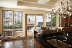Patio doors and large windows make a wall of glass in penthouse kitchen.
