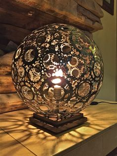 Artist Toby Boswell of Pale Rider Handmade has perfected a metalworking process to create these wonderful spherical lamps from recycled bicycle gears. and sits on a wood base…