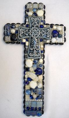Classic blue delph-like cross in the center of a beautiful blue and white cross. The cross contains jade, marble, quartz, ceramic, tile, glass beads and glass blocks.