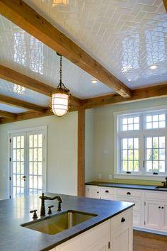 Yankee Barn Homes - Herringbone subway tile on the kitchen ceiling + reclaimed wood beams. Completely beautiful.