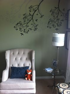 Nursery works Empire Rocker under painted birds and branches accent wall stencil.