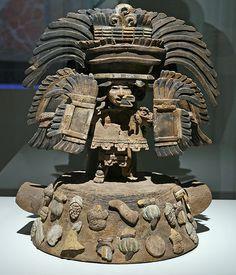 Teotihuacan, Oztoyahualco Período clásico, 350 - 550 d.C. Arcilla y pigmentos 41 x 33 cm Zona Arqueológica de Teotihuacan  La ornamentación de la nariz es parecida a la del dios de la guerra Quetzalpapalotl, por lo que se infiere que se trata de un guerrero fallecido. Está parado sobre el Tonacatepetl (montaña del sustento) caracterizado como tal por la representación de alimentos.