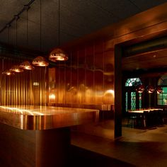 Swiss architect Aurélie Blanchard has lined every wall and surface in the bar of this Basel restaurant with copper, while a dark green dining room looms just behind.