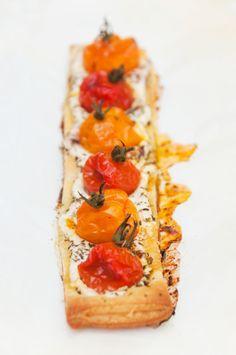Feuilletés aux tomates cerises - recette facile 1 pâte feuilletée toute prête 24 tomates cerises (12 rouges et 12 jaunes orangées) 135 g de fromage frais 2/3  pincées d'origan séché Quelques brins de ciboulette 4 olives noires dénoyautées Poivre du moulin