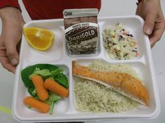 Locally sourced salmon served with rice, cole slaw, garden salad and an orange slice in Juneau School District, AK!