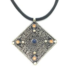 "Embellished is a 20"" Long Necklace Using Soft Black Deer Hide and Sterling Silver Toggle. The Pendant is of German Silver Finished in an Antiquing and Embellished With Blue Lapis and Gold Swarovski Crystals. Product #15-079"