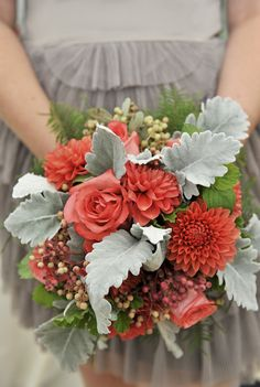 wedding bouquet with roses and dahlia in lovely corals with dusty miller, greenery, and berries.