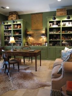 masculine home office with green built in bookshelves and a hide rug