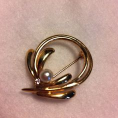 Gold tone brooch with faux pearl and diamond. Elegant little gold tone brooch. Faux pearl and diamond accent. No flaws Jewelry Brooches