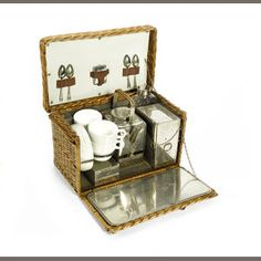 A four person picnic set by G W. Scott & Sons, London, circa 1905, wicker basket, with lid and fall front opening to reveal fitted interior, with rectangular kettle, burner, four china cups with saucers, metal food boxes, glass bottle, the lid with spoons and vesta case behind leather straps, the case 14in wide.