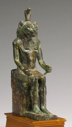 Egyptian bronze figure of Lion-headed Maahes, Late Period, 716-30 B.C. Enthroned with his hands resting by his knees, and wearing a striated kilt with central tab, broad collar, and striated tripartite wig surmounted by a uraeus, the ruff and whiskers carefully engraved, the throne engraved on the sides with a scale pattern and on the back with a scale pattern beneath papyrus and lotus flowers, 21.6 cm high. Private collection