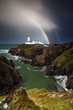 Fanad Head lighthouse captured as a double rainbow forms behind it, Ireland.
