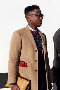 Shop this look on Lookastic:  https://lookastic.com/men/looks/overcoat-gilet-crew-neck-sweater-dress-shirt-jeans-gloves-sunglasses/7804  — Black Sunglasses  — White and Black Polka Dot Dress Shirt  — Navy Gilet  — Red Crew-neck Sweater  — Camel Overcoat  — Red Leather Gloves  — Navy Jeans