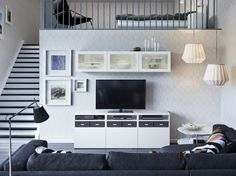 A living room with a white TV bench with white drawers and wall cabinets with white doors and tempered glass panels.
