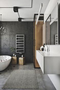 I love unique bathroom decor, & this one certainly is that. Love the concrete floors & dark walls. The plants & super large tub don't hurt either!