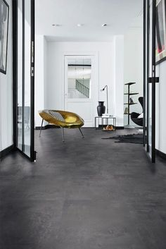 Painted Black laminate flooring in a contemporary living space. We love the black vase and the gold seat! Living Room Tiles, Grey Flooring, Room, Tile Floor Living Room, Dark Tile Floors, Living Room Flooring, Black Laminate Flooring, Flooring, Upholstery Cost