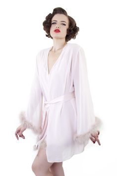 This robe is made for all things bombshell, pinup, and burlesque. Inspired by the always inspiring Bettie Page, it's the slinkiest retro vintage-inspired robe you could find.   Sheer baby-pink chiffon Trimmed with pale mink-hued feather on the sleeve hems Wide sleeve Ties together with a matching satin tie, with two feathery puffs on each end Pair with the Ostrich Feather Babydoll for ultimate bombshell inspiration