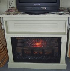 "Faux fireplace made from an old TV cabinet - removed the doors - painted inside black - added electric logs - rearranged the trim and added a panel that hides the DVD player - cost me less than $20 to complete ... the grate is handmade, too, to accommodate the depth of the cabinet - copied from my real one - used wood scraps painted black to look like iron - finished off with a tension curtain rod and scrap piece of screening  to complete the look.  I have this ""fireplace"" on my back porch…"
