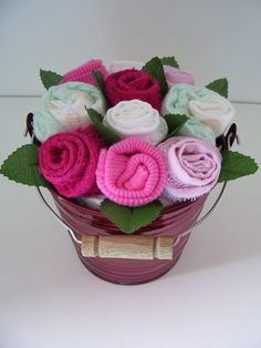 Basket full of posies made of baby items.