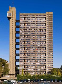 Trellick Tower. Tall building block. Which has an unusual look as it has a block which is only connected to the flats by 9 small corridors. This building uses blocks of squares. This architecture uses a dull plane brown colour.