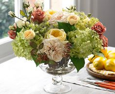 The perfect antidote to a dull day, this silk flower centrepiece radiates light from the yellow old English roses at any time of year and is subtly complemented by ivory and terracotta roses.