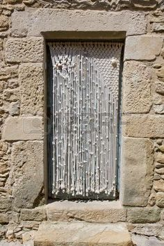Macrame door curtain in an old stone house...but what's behind it? whose story takes place behind it?