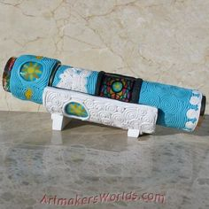 A hand made, polymer clay filigree covered functional oil cell kaleidoscope with matching stand.