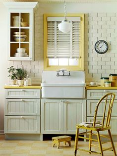 I love this look.  Farmhouse style kitchen with subway tile backsplash, apron front sink, beadboard style cabinets with glass doors on the upper cabinets.  I also love the pop of color.