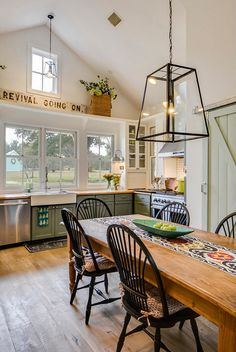Beautiful farmhouse style kitchen with band sawn plank floors, vaulted ceilings and an antique sign.