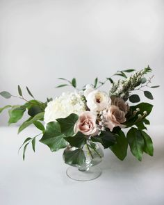 Wedding centrepiece with white hydrangea, eucalyptus, quicksand roses and white ranunculus in a clear glass pedestal vase