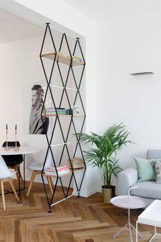 Minimalist living room with herringbone wood floors, a geometric bookshelf…