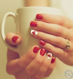 red nail polish. white accent nail with heart. manicure