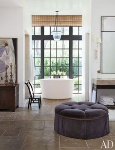 When it came to building a new home for their extended family, Don and Rela Gleason, Napa residents, wanted something relaxed yet stylish. Designed by Rela, an interior decorator, and architect Bobby McAlpine, the master bath is airy and open, with soaring ceilings and a rustic concrete-title floor. Modern elements mix happily with heirloom antiques; the concrete soaking tub overlooks an enclosed private terrace | archdigest.com