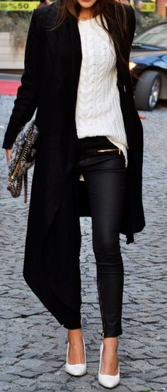 Black coat over white sweater and black pants.