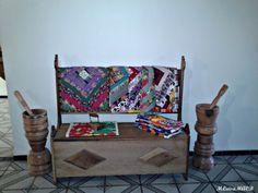 Pilão, banco baú, e tapetes de retalhos.
