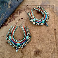 Delicate teardrop earrings with teal, aqua, and gold colors.  Smaller brass teardrops form the base of these beaded earrings. I wove tiny seed beads around the perimeter of the hoops with larger translucent aqua faceted accent beads. The colors are inspired by the blues and greens and purples of peacock feathers. Each bead is secured to the base frame using multiple passes of Nymo thread, a sturdy multifilament cord favored by bead weavers.  These earrings are lightweight for their larger…
