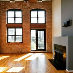 Loft apartment for rent in Chicago with lovely high ceilings, natural light and fantastic factory windows. Private balcony off living room in Chicago loft apartment that also features a gas burning fireplace, hardwood floors and exposed brick walls. Exposed Brick Apartment, Exposed Brick Walls, Rustic Apartment, Chicago Lofts, Chicago Apartment, Apartment Sites, Loft Apartments, Niche Decor, Loft Floor Plans