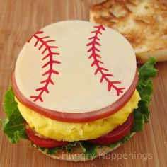 This Breakfast Sandwich could be made into a tennis ball...website does this with a slice of cheese...make a baseball, football, golf ball, tennis ball, basketball, soccer ball, volleyball, or 8 ball.