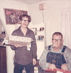 Crazy one stands in corner of dining room waiting to give ragged wrap birthday present to bib overalls dad in specs and cigarette as Monkees look down from wall poster behind. 1960s vernacular photo snapshot - www.reservatory.net
