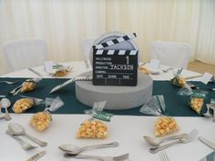 """Along with a good friend we made the clapper board centre pieces by spray painting a 15"""" x 3"""" foam circle as the base. Then taking an old sweet tin (celebrations/heroes etc) we glued a film strip around the tin to make a movie reel. We then bought clapper boards and wrote a director name and table number to correspond with the oscar seating plan. The reverse side of the reel had a film poster to inform guests of a film made by the director table they were sat at."""