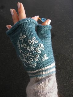 Cute knitted fingerless gloves with embroidered snowflake.