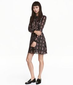 Black/roses. Short dress in chiffon with a printed pattern. Collar with ties, buttons at top, pin-tucks and ruffles at front, and long sleeves with